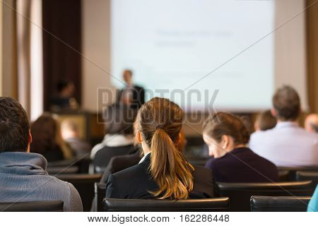 Speaker at Business Conference and Presentation. Audience in the conference hall. Business and Entrepreneurship. Copy space on white screen.