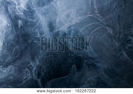 Abstract acrylic paint swirls in water on black background