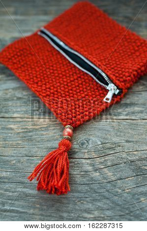 Close up of a handmade knitted purse with beads and tassel