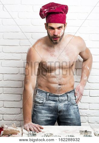 Handsome man or muscular cook baker in red chef hat poses with flour on sexy muscle torso body with six packs and abs on kitchen wall