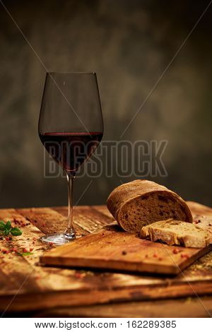 Still life with glass of wine and ciabatta bread