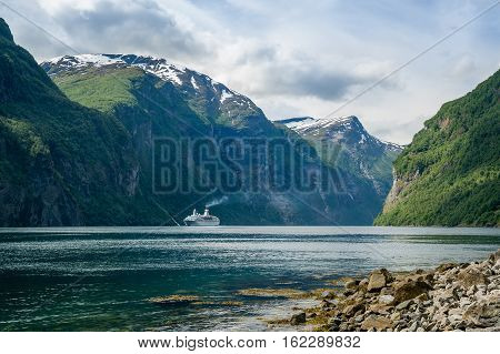 Touristic cruise ship is entering steep Geiranger fjord shores, Norway.