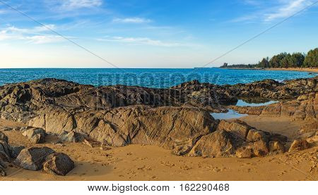 Beautiful seascape with sea and rock in Nang Thong Beach, Khao Lak, Thailand. View of bright blue sea with protruding stones and fishing boats. Nature composition.