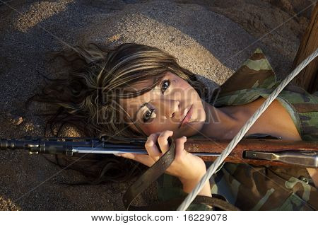 Beautiful young woman in Army Flak jacket laying on desert ground holding wire and rifle