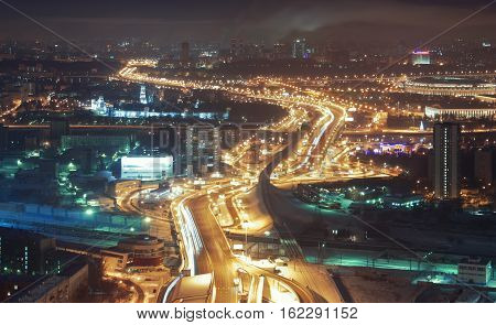 Giant automobile overpass at night view from above in winter. Soft focus