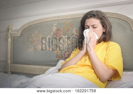 Brown-haired girl blowing her nose while laying in the bed
