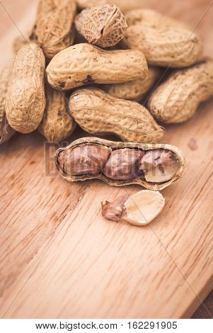 Close up of a bunch of peanuts on wooden background.