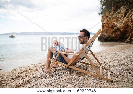 Handsome young man with his baby son at the beach, sitting on deckchair, enjoying time at seaside.