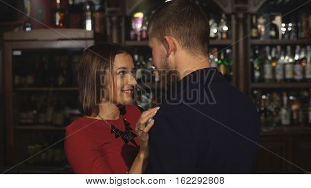 beautiful woman in red dress seducing a man in a bar and drinking champagne