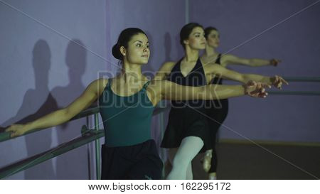 Ballerinas Practicing At Ballet Barre In the classroom