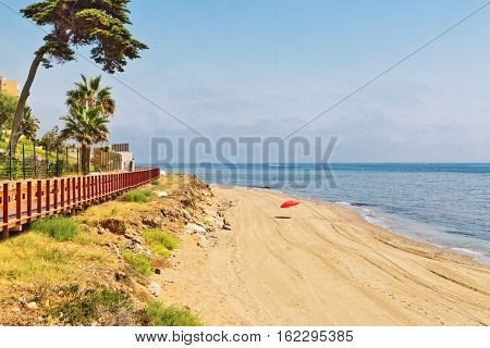 Lonely red umbrella on the beach in Costa del Sol, Andalusia, Spain