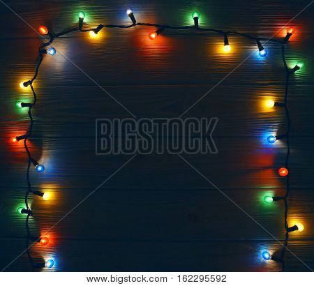 Christmas colorful lights frame background  on wooden table with copy space