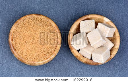 Brown sugar in a bamboo bowl on slate
