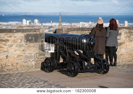 Edinburgh UK - November 06 2016: Girls standing near a Castle siege gun on a wall and enjoying the view