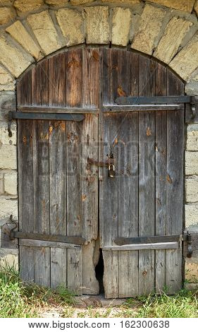 Facade of an old stone building of limestone and wooden door