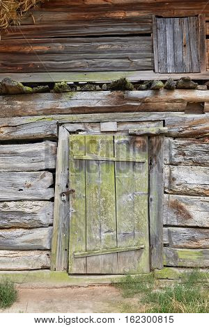 Facade of an old rickety wooden building with a door