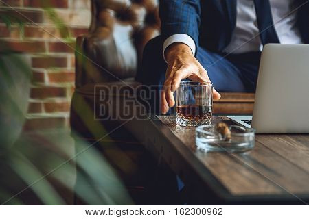 Close up of male hand getting alcohol beverage. Businessman is sitting on couch and working at computer