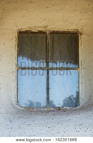 Window in the rural house in Ukraine in the second half of the nineteenth century. In the window reflected sky and a thatched roof