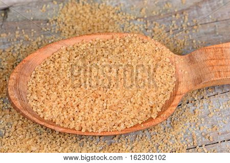 Beige sugar in a wooden spoon on table