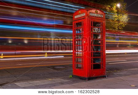 London Great Britain - October 30 2016: Long exposure shot of the iconic red telephone booth with the traffic light on the background