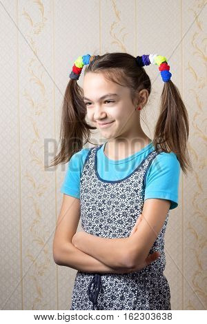 portrait of a smiling 11 year old girl with funny tails standing with arms crossed.