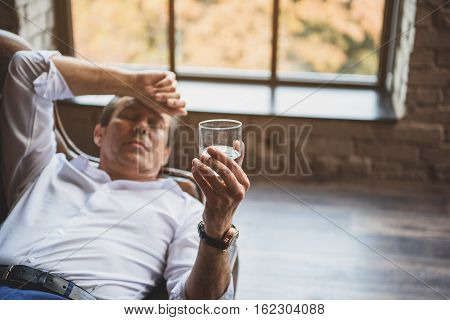 Tired exhausted man is lying on sofa. He is touching his forehead with hand and holding amber beverage. Depression concept