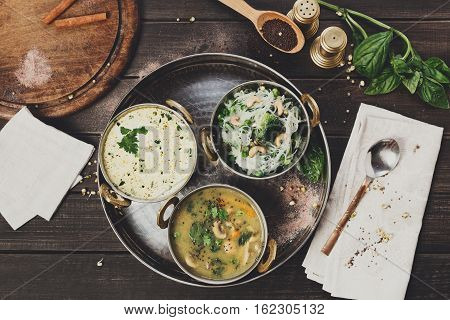 Vegan or vegetarian restaurant dishes top view, summer yoghurt raita, rice and mushroom soup in copper bowls. Traditional indian cuisine meal assortment on wood background. Healthy eastern local food