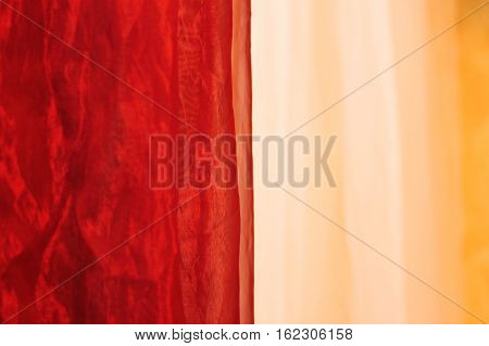 Soft coral and beige chiffon, fabric texture, textile background. red and beige tulle hanging at the entrance to a massage parlor