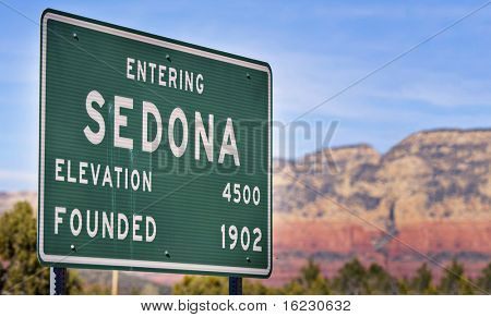 Entering Sedona Arizona, USA, road sign with red rock mountains visible in background.