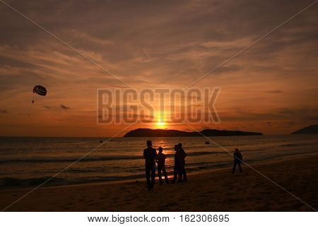 silhouette of parachute and people at the beach