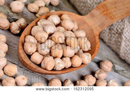 Chick peas in a wooden spoon on table
