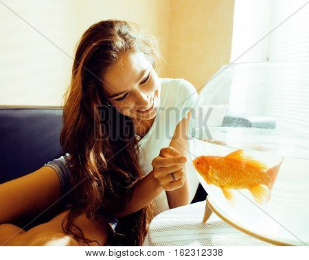 pretty woman smiling playing with goldfish at home, sunlight morning, lifestyle people concept close up