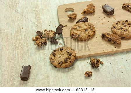 A photo of crunchy chocolate chips cookies with crumbs and chocolate pieces around it, with copyspace, selective focus