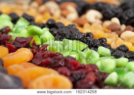 Background of mixed dried fruits (raisins, apricots, figs, prunes, goji, cranberries, blueberries, prunes) and nuts (almonds, hazelnuts, peanuts, cashews). Closeup.