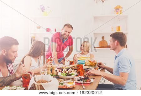 Group of happy young people laugh and chat at dinner table, party for friends indoors at cafe or home. Friendship, relax at holidays and week-end. Men and women sitting with various dishes.