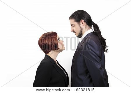 Stand off between a male and female partner with the shorter woman staring up belligerently into the face of the man in a suit with a ponytail profile view on white