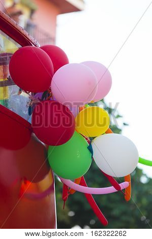 Low angle view on detail view of various balloons attached to back of red vehicle outside