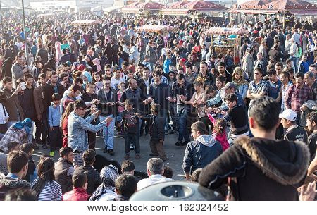 ISTANBUL TURKEY - APRIL 12 2015: Sunday afternoon in the Eminonu pier resting and dancing people. Eminonu district is one of the most populer shopping and historic destination in Istanbul.