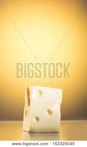 Yellow cheese with holes on a yellow background
