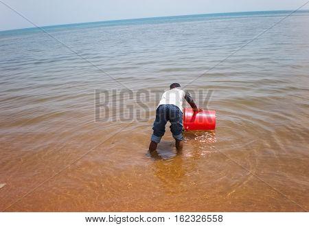 Congolese draws water on Tanganyika lake in Kalemie with red bucket