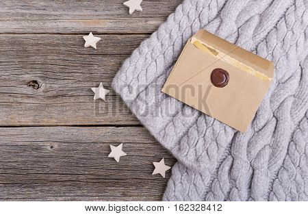 Winter scarf and the letter on the background of the old wooden boards.