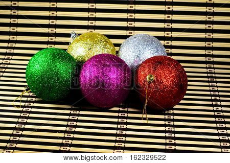 Colored christmas balls on a bamboo mat