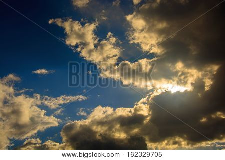 Bright sun behind dark Cumulus clouds against the dark blue sky.