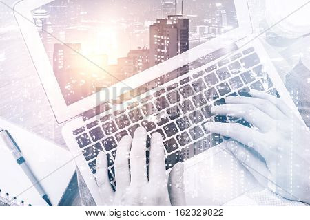 Male hands using laptop on city background. Double exposure. Communication concept