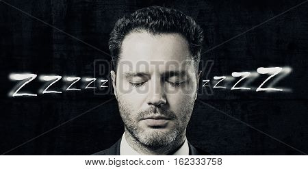 Portrait of handsome man sleeping on dark background. Sleep concept