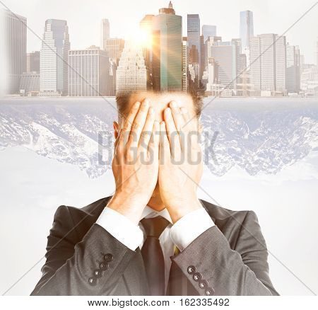 Businessman covering face with hands on abstract city background with sunlight. Double exposure. Future concept