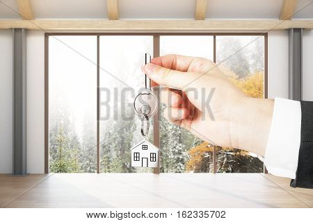 Close up of hand with key in modern interior with panoramic landscape view. Mortgage concept