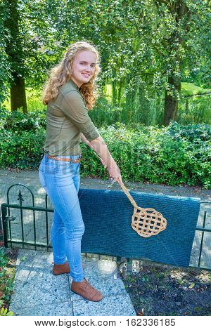 Caucasian teenage girl beating door mat with carpet beater