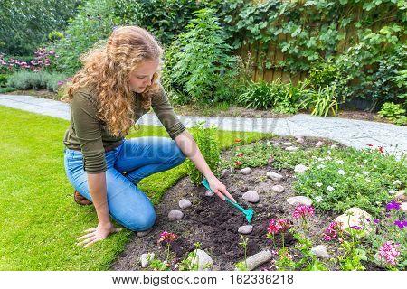 Dutch teenage girl working with rake outside in garden