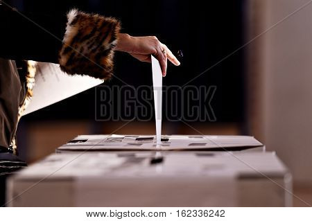 Hand with a stamp casting a vote into the ballot box during elections
